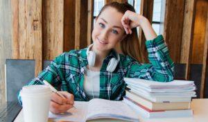 Glad tjej antecknar i en bok
